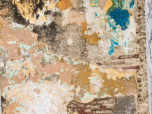 wall with many coats of paint and plaster